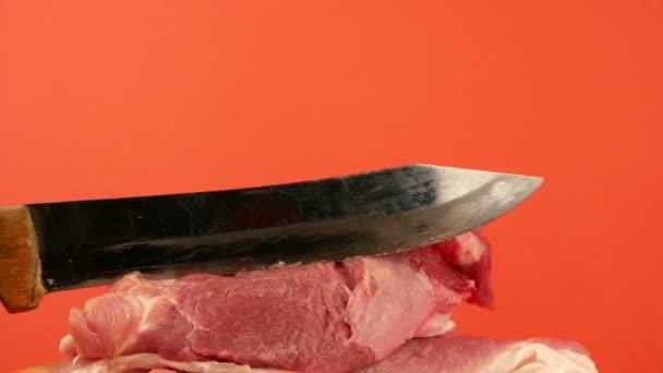 Úzký nůž krájí kus červeného masa. Téma obchodu s masem. Krájení vepřového. Čerstvé syrové červené maso Selektivní zaměření, mělká hloubka pole