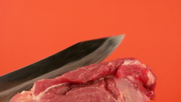 Detailní záběr velkého kuchyňského nože krájí čerstvý syrový kus masa na jasně oranžovém pozadí. Krájení vepřového masa. Vařím čerstvé maso. Masový kuchyňský nůž. Selektivní zaměření, mělká hloubka pole