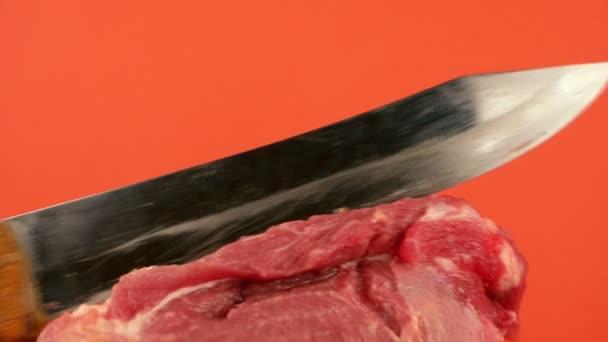 Detailní záběr velkého ostrého nože, který odřezává kus syrového červeného masa na jasně oranžovém pozadí. Masné výrobky. Vaření vepřového masa. Selektivní zaměření, mělká hloubka pole