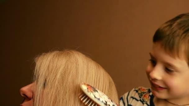 Roztomilý usmívající se běloch česající vlasy své blonďaté matky hřebenem. Dětský salón krásy. To dítě dělá mámě vlasy. Selektivní zaměření