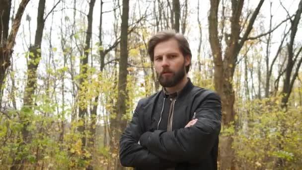 Krutý běloch s vousy, který stojí v podzimním parku a dívá se do kamery a narovnává si vlasy. Sebeizolace během epidemie
