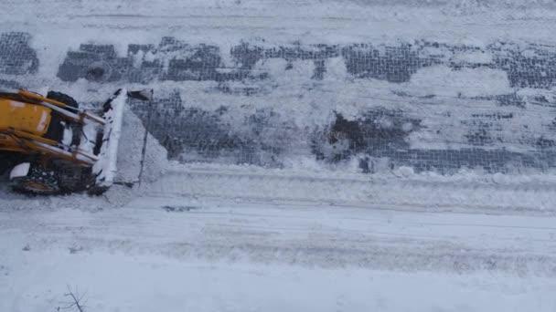 Ein gelber Bagger schaufelt die Straße vom Schnee. Schlechtes Wetter für die Räumung der Straßen durch den Straßendienst. Rahmen von oben
