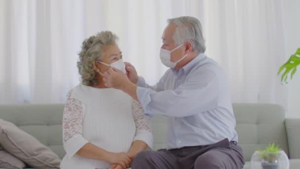 Šťastné asijské starší nebo senioři pár nosí lékařskou masku společně, aby se zabránilo koronavirus sedí na pohovce v obývacím pokoji doma, Nový normální životní styl staršího pobytu doma