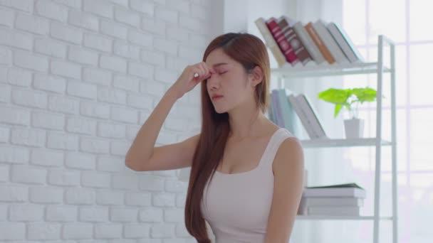 Asijské mladé žena má migrénu a bolest hlavy po probuzení v útulné ložnici doma, Náhle bolestivý útok na masáž hlavy kolem na místě bolesti, Zdravotní péče koncepce