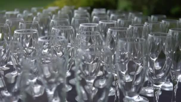 Křišťálové sklenice jsou připraveny k oslavě. Šumivá jídla na stole ve venkovní restauraci. Spousta skleniček na bohaté svatební hostině.