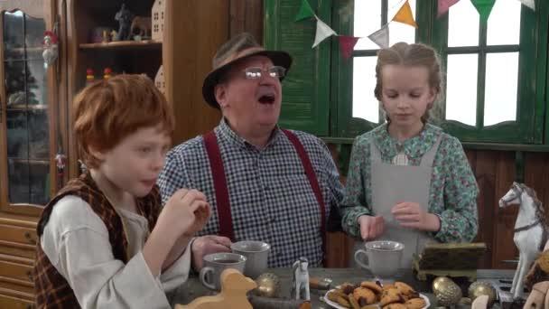 4K. V truhlářské dílně, Geppetto tesař Papa Carlo pije čaj se svým vnukem a vnučkou. Dětské pohádky. Dřevěná panenka s dlouhým nosem. The Creation Of Pinocchio.