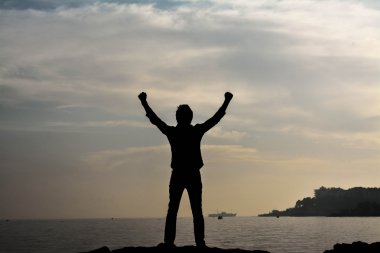 Man on the sea background silhouette: Celebrating win