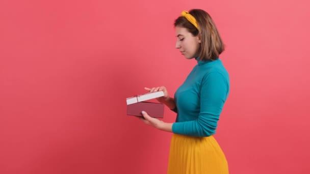 Close up of a happy woman opening gift box over red background.