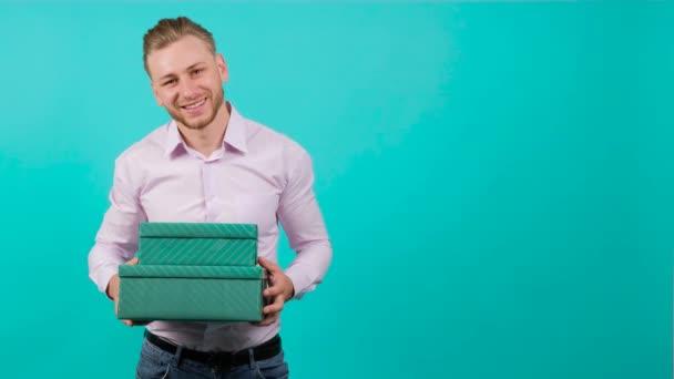 Fiatal jóképű férfi, aki szívből ad egy ajándékdobozt, a kamerába néz..