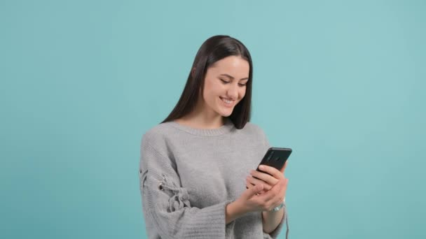 Nahaufnahme einer jungen Frau, die ein lustiges Video auf ihrem Smartphone anschaut.