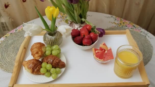 Close up of a wood tray with orange juice, fruits croissant and flowers, put the cup on.