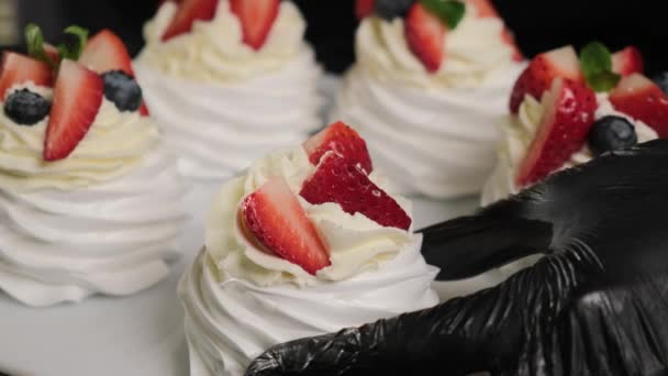 Pastry chef decorates Anna Pavlovas cakes with fresh fruiets and mint leaves.