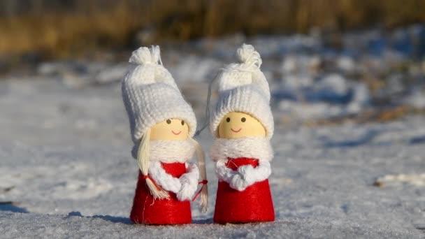 Detailní pohled na pár hraček stojících ve sněhu. Hračky vypadají jako dva milenci v červených šatech a bílých pletených čepicích. Téma Valentýna.