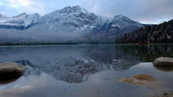 Kanoe se klidně vznáší na vodě jezera s fantastickými odrazy hory a okolí, bezprostředně po prvním sněhu, Pyramida Lake za soumraku, Jasper, Kanada.
