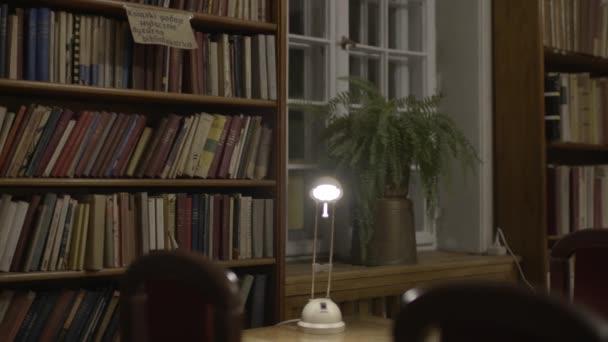Kamera, veřejná knihovna s tlumenými světly, se pomalu pohybuje a odhaluje další židle a stoly. klip 4K (S-Log), Varšava, Polsko.