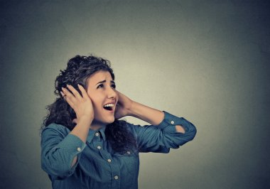 Unhappy stressed woman covering her ears looking up stop making loud noise