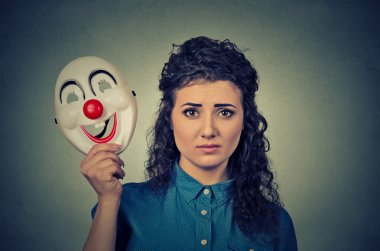 upset worried woman with sad expression holding clown mask expressing cheerfulness