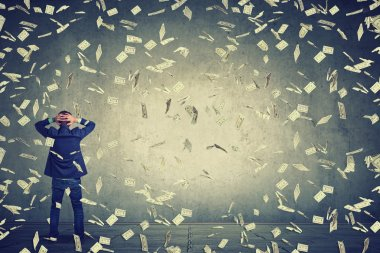 business man standing in front of wall under money rain dollar banknotes falling down