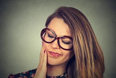 woman in glasses with sensitive toothache crown problem about to cry from pain
