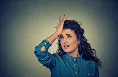 silly young woman, slapping hand on head having duh moment