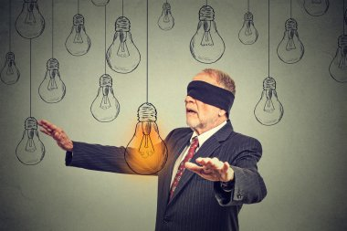 Blindfolded senior man walking through light bulbs searching for bright idea