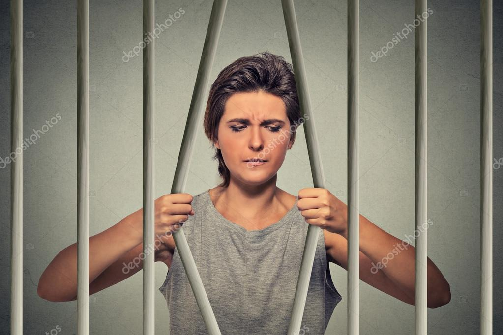 Stressed desperate sad woman bending bars of her prison cell
