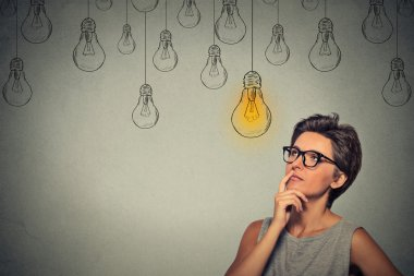 Portrait thinking woman in glasses looking up with light idea bulb above head isolated on gray wall background stock vector