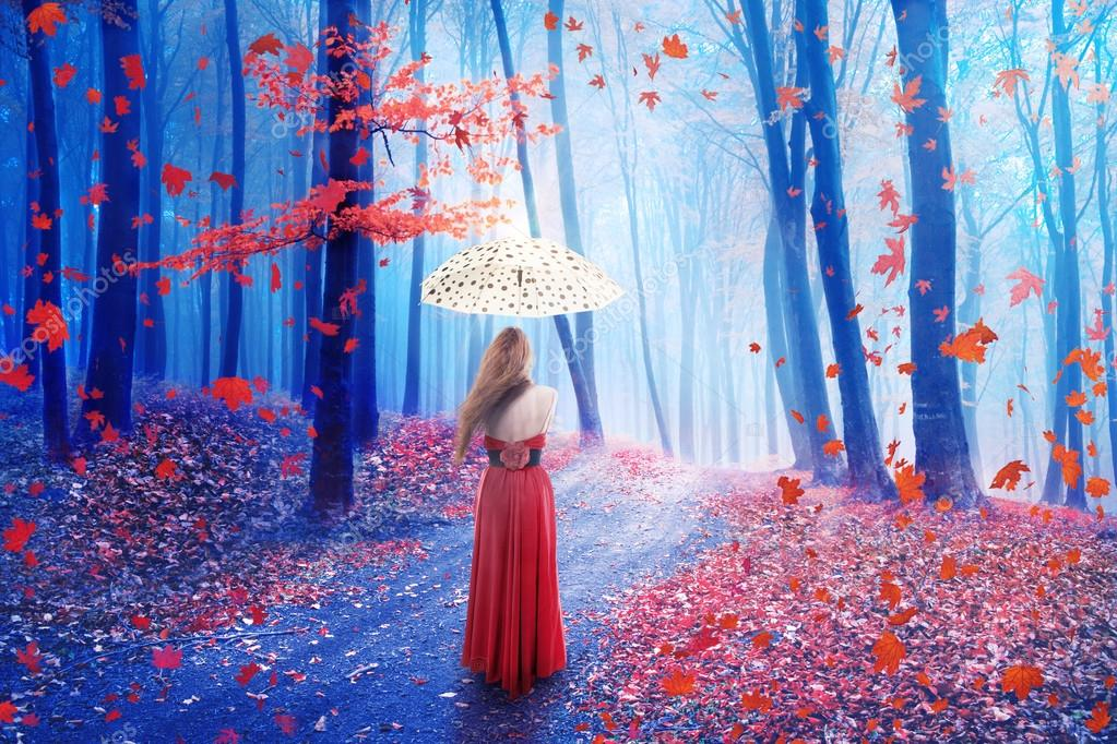 Fantasy image lonely woman with umbrella walking in forest in fairy dreamy realm.