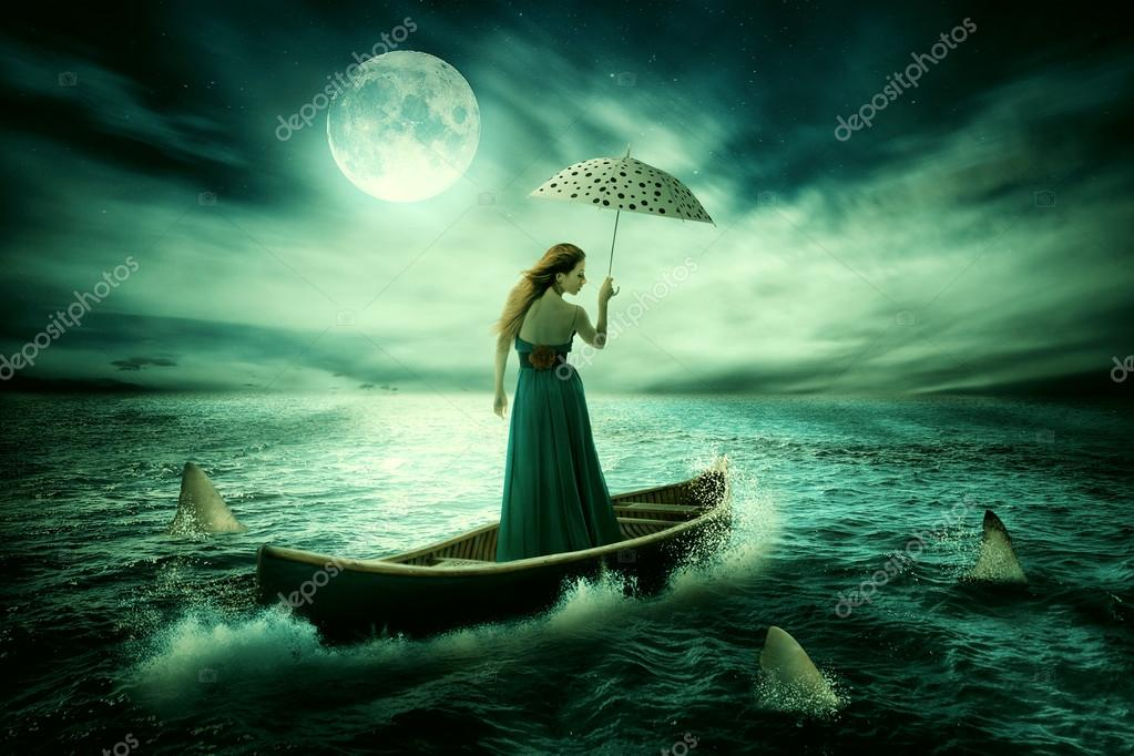 Young lonely woman with umbrella drifting on boat after storm surrounded by sharks