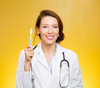 Smiling dentist with toothbrush isolated on yellow background