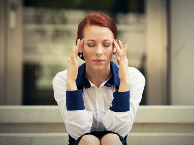 stressed sad woman sitting outdoors having headache. City urban life style stress