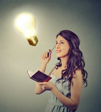 beautiful girl thinking planning looking up at bright light bulb