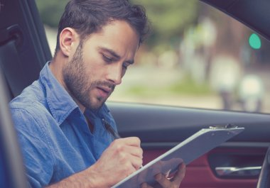 transportation ownership concept. Man inside new car reading signing documents