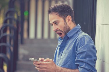 Closeup portrait anxious young man looking at phone seeing bad news message or photos with disgusting emotion on his face isolated outside city background. Human emotion, reaction, expression stock vector