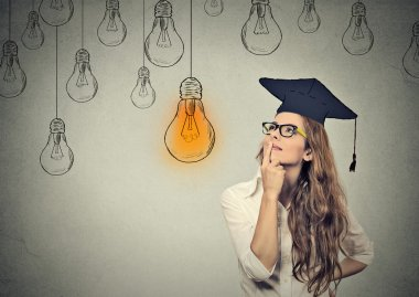 thoughtful graduate student young woman in cap looking at bright light bulb