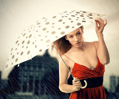 Young pretty woman in red dress with umbrella under rain on a night dusk city background. Rainy weather stock vector