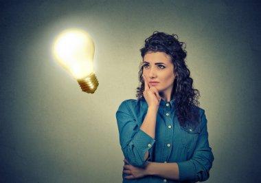 Woman thinking dreaming looking up at bright light bulb