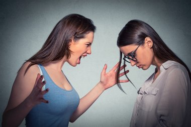 Angry woman abusing screaming at another scared nerdy one in glasses