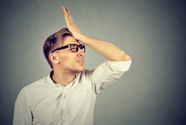 Silly man slapping hand on head having duh moment
