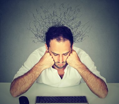 Sad man with brain melting into lines looking at computer keyboard