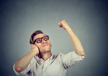 young man covering his ears from loud noise, having headache
