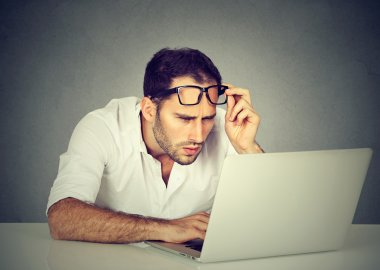 man with glasses having eyesight problems confused with laptop
