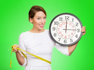 Happy, fit woman holding clock, measuring her waist with tape