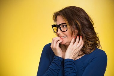 Closeup portrait nervous woman with glasses biting her fingernails craving something, anxious isolated yellow background copy space. Negative human emotion facial expression body language perception stock vector