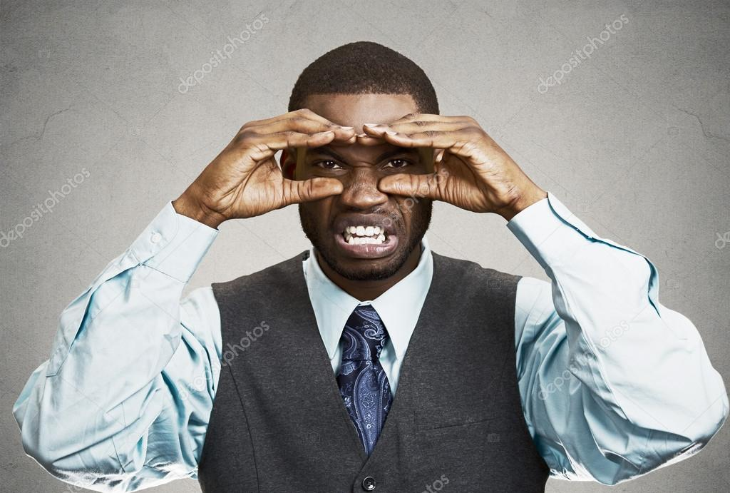 man with disgusted face expression looking through hand binocul