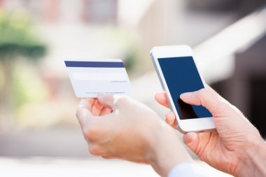 Woman hands holding credit card and using cell, smart phone