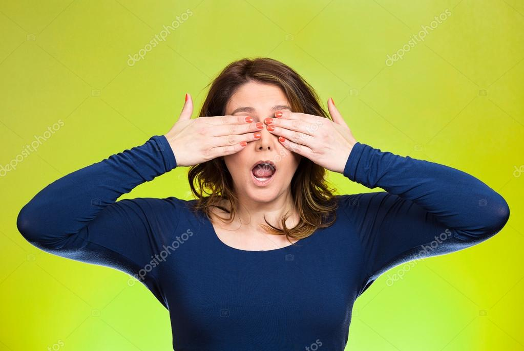 Woman closing eyes with hands can't see. See no evil concept