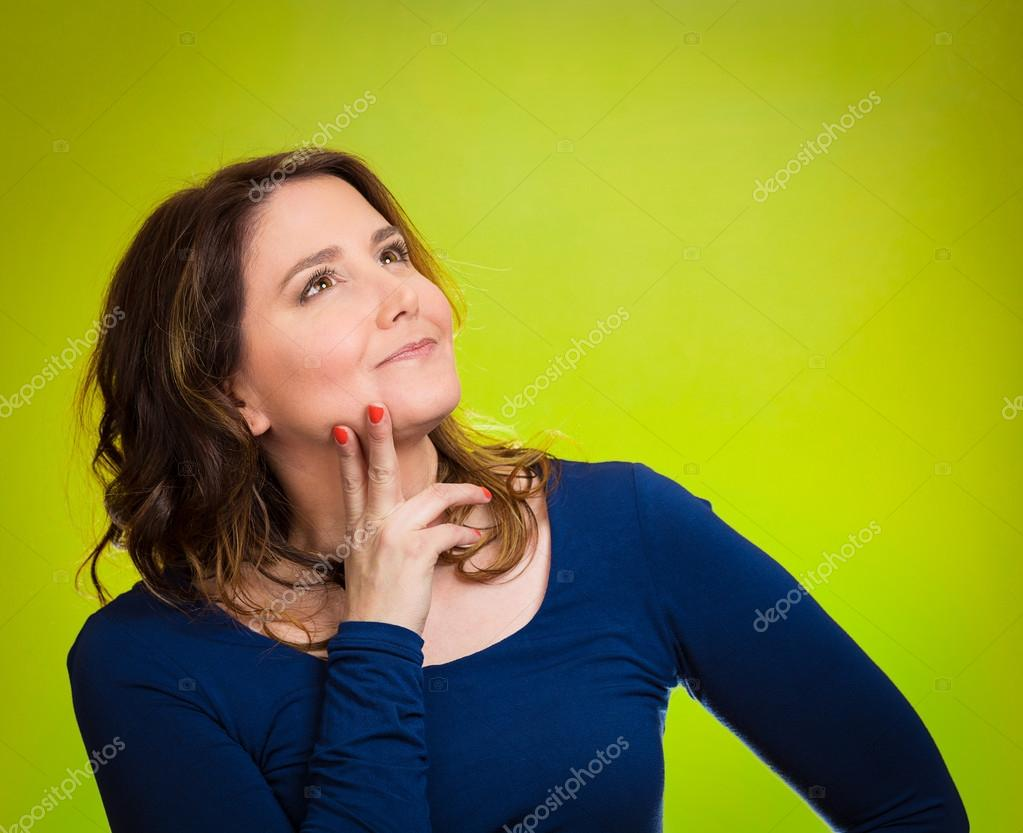 Happy, middle aged woman looking upwards daydreaming