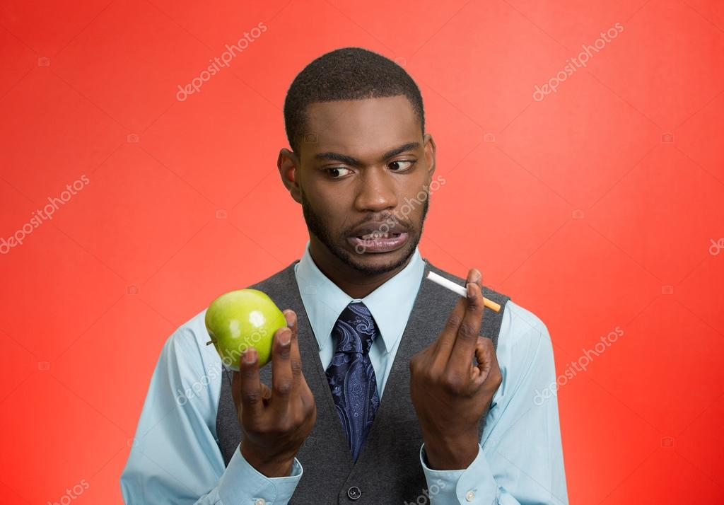 Man deciding on healthy life choices, craving cigarette versus green apple
