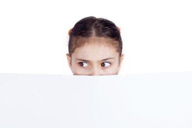 Suspicious teenager, scared, hiding behind blank paper billboard